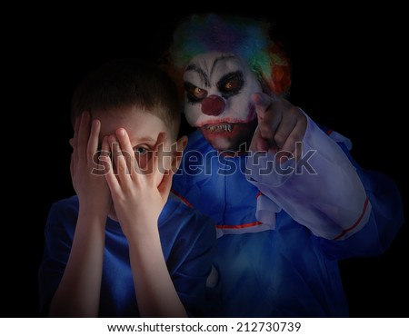 A child is hiding his eyes in the dark night and looks scared and upset at creepy clown. The boy is isolated on a black background for a fear concept. - stock photo