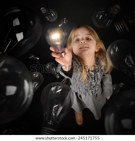 A child is holding up a bright glowing light bulb with dark light bulbs around her on an isolated black background for an education or academic concept. - stock photo