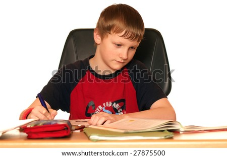 A child is sitting at the desk and makes his homework