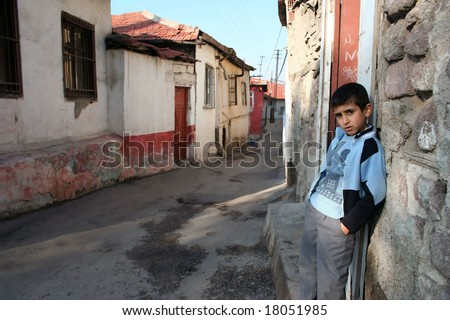 A child is standing in front of his house - stock photo