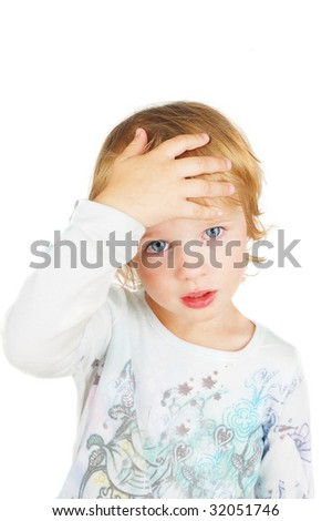 A child looks sad while, tired  an  checks her forehead for fever - stock photo