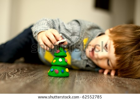 a child making a snowman and christmas tree of plasticine - stock photo