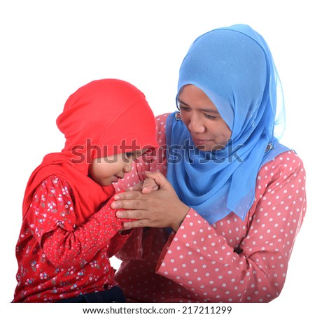 A child Muslim women greeting to elders. Mother and his Daughter. - stock photo