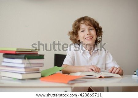 A child of primary school age do homework. The boy does his homework at his desk at home, looking at the camera and smiling. - stock photo