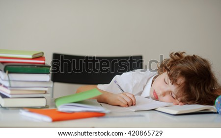 A child of primary school age do homework. The boy does his homework at his desk at home. The student / pupil has been bored on the lesson. Boy fell asleep during homework. Lovely first grader. - stock photo