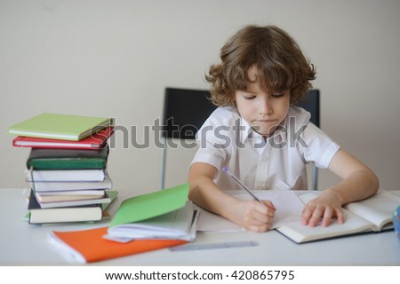 A child of primary school age do homework. The boy does his homework at his desk at home. The student / pupil has been bored on the lesson.  - stock photo