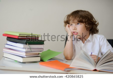 A child of primary school age do homework. The boy does his homework at his desk at home. The student / pupil has been bored on the lesson. Lovely first grader. - stock photo