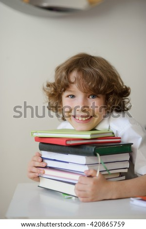 A child of primary school age do homework. The child holds a book in his hands and feels the emotion, enthusiasm. - stock photo