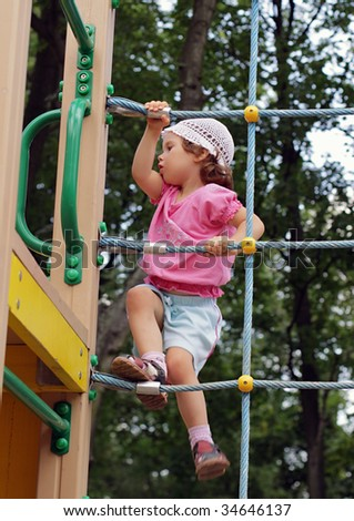 A child on outdoor playground equipment. Three years old