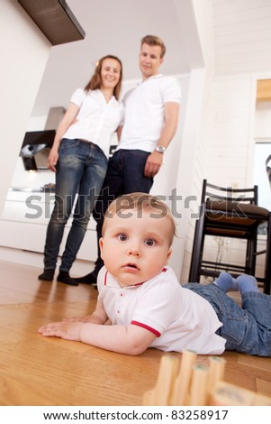 A child on the floor looking intently at the camera, parents in the background - stock photo