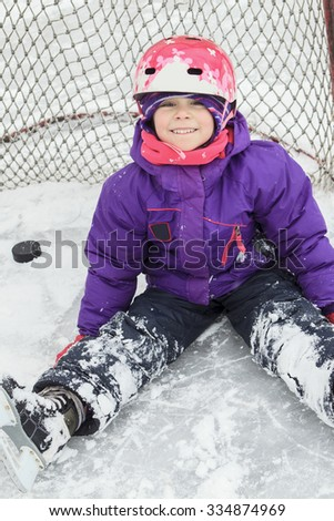 A child on the hockey ice with a puck.