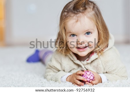 A child on the rug at home - stock photo