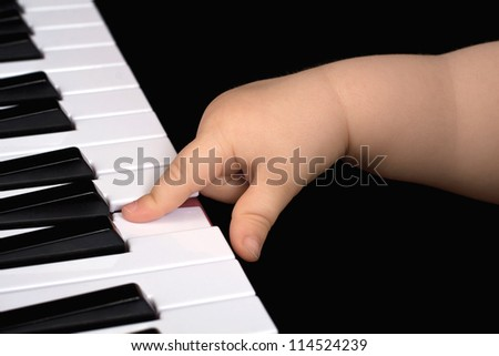 A child one year old plays with one finger piano in front of a black background - stock photo
