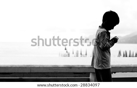 A child playing and walking along the seaside - stock photo