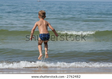 A child playing at the beach with waves