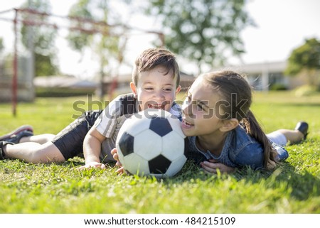 A child playing football on field with sister