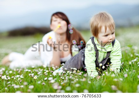 A child playing outdoors. Beautiful mother watches in the background. - stock photo