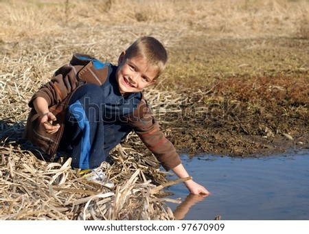 A child playing outside and learning about nature while getting messy in a wetland pond, with tadpoles in hand