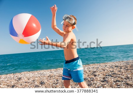 A child playing with beach ball near the sea