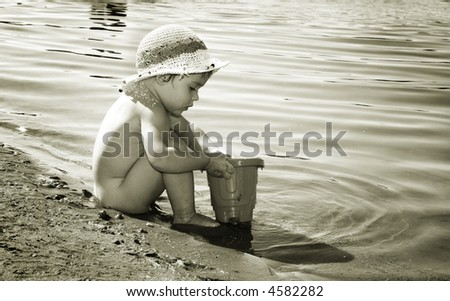 A child playing with water and sand on a beach - stock photo