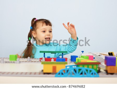 A child plays with a toy railroad on table - stock photo