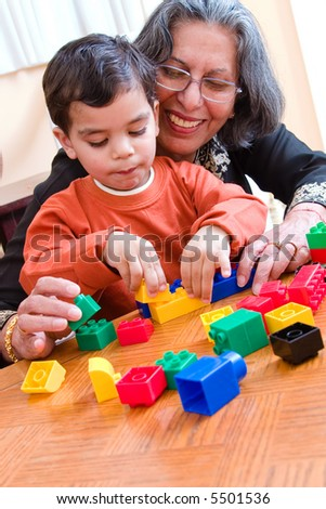 A child plays with his blocks while his grandmother helps him - stock photo