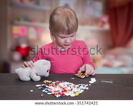 A child plays with pills and a syringe. Girl gets pill capsule from the blister. Near Toy - a white teddy bear. Tablets are many, they are colorful. Risk games with pills - stock photo
