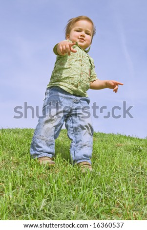 A child pointing at camera, against blue sky - stock photo