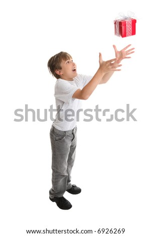 A child reaches high to catch a falling present.  Suitable for Christmas, birthdays, etc. - stock photo