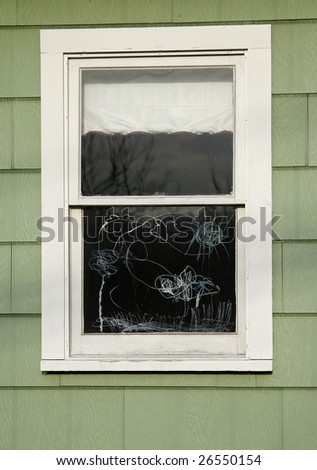 a child's crayon scribble drawing on a house window