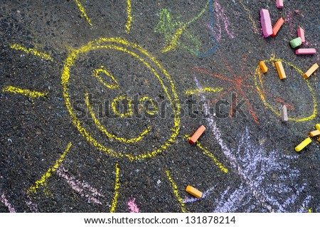 A child's drawing of sun and colorful chalks on a street, a sidewalk or a pavement.