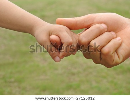 A child's hand holding an adult's finger - stock photo