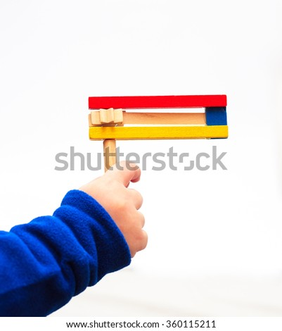 A child's hand holding Colorful wooden noisemaker Purim holiday - stock photo