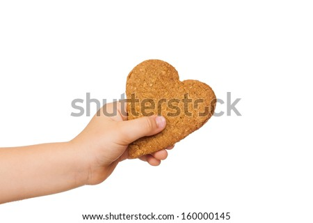 A child's hand is holding a love shaped gingerbread cookie. Isolated on white. - stock photo