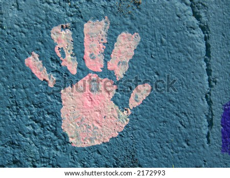 A child's handprint in pink paint on a blue wall. - stock photo
