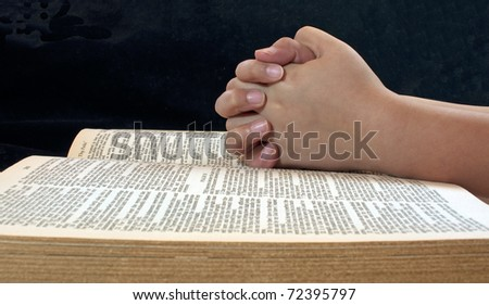 A child's hands folded on an open Bible - stock photo