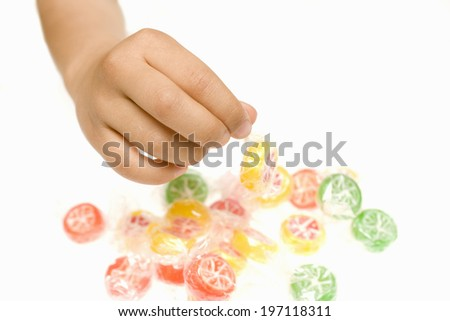 A Child'S Hands Unwrapping A Candy - stock photo