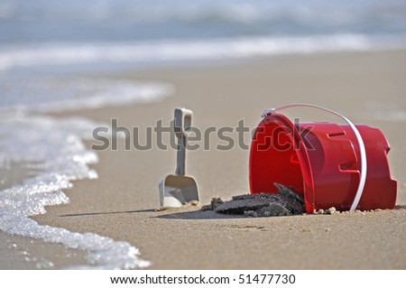 A child's sand bucket at the beach - stock photo