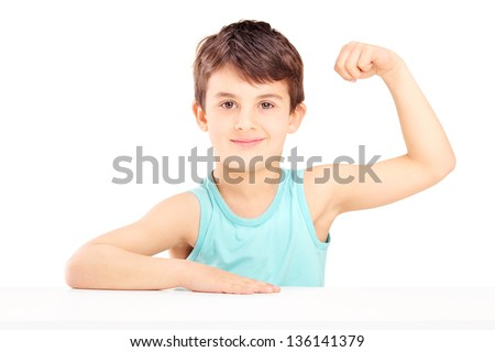 A child showing his muscles seated on a table isolated on white background - stock photo