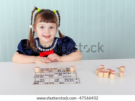 A child sitting at a table and played with bingo - stock photo