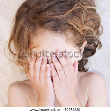 a child throwing a tantrum lying down on the floor with her hands covering her face - stock photo