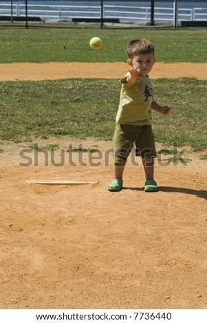 A child throws a ball outdoors in portrait orientation - stock photo