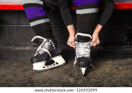 A child ties hockey skates in arena dressing room - stock photo