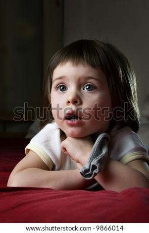 A child totally taken by watching a cartoon on TV - stock photo
