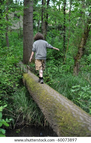 A child walking across a fallen tree going across a river in the woods - stock photo
