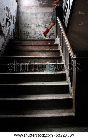 a child walks up an old stairway littered with broken glass - stock photo