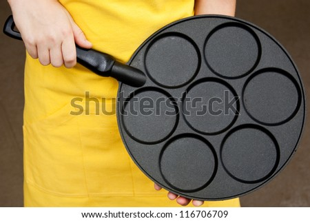 A child wearing a bright yellow apron holding an empty pancake pan