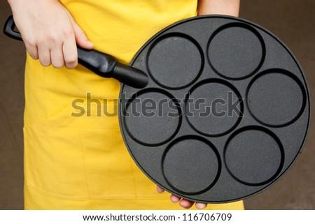 A child wearing a bright yellow apron holding an empty pancake pan - stock photo