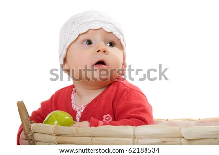 A child with an apple sitting in a basket. - stock photo