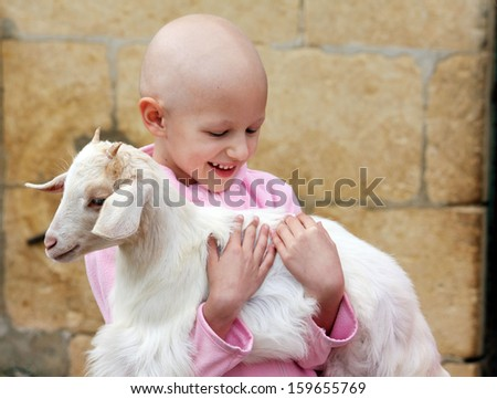 a child with cancer carrying a goat  - stock photo